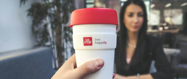 red and white to go mug made by Illy and a businesswoman in the background